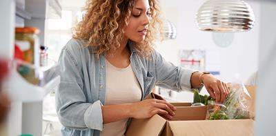 woman unloading food shopping fridge