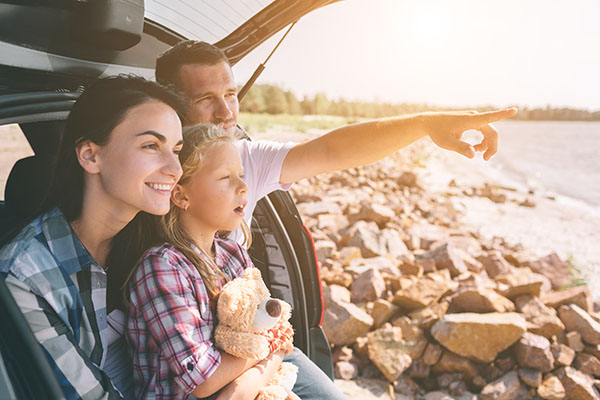 Young family in car boot looking at landscape