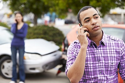 Man on the phone and woman on the phone in the background after a traffic collision