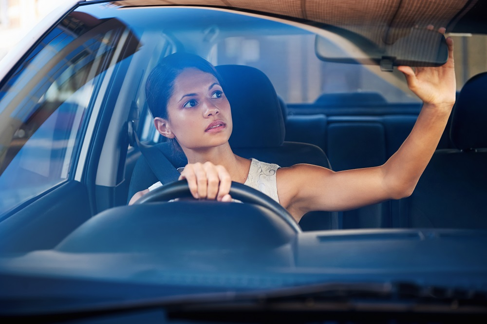 Young woman in car adjusting rearview mirror