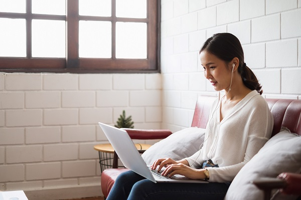 Asian woman sitting with laptop at home