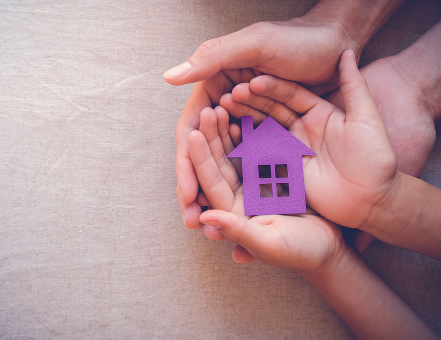 Hands holding a purple house