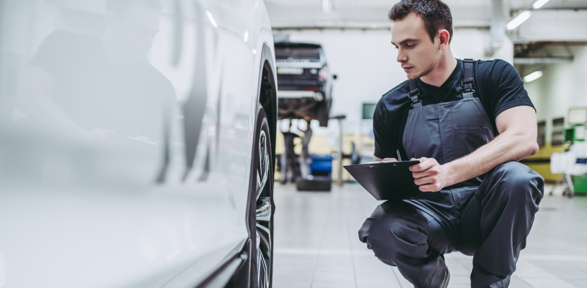 man inspecting car in factory production line