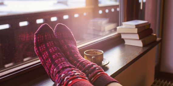 woman with socks on in warm home during winter
