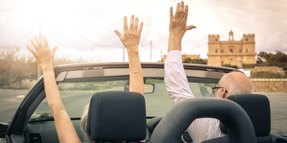 man and woman in car waving hands in the air happily