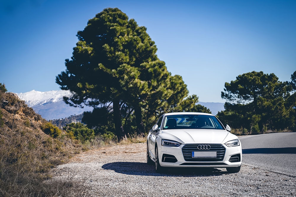 White Audi on the road in mountains