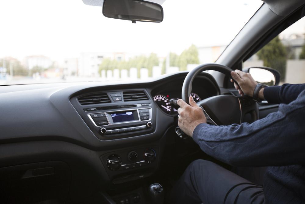 Man holding steering wheel driving