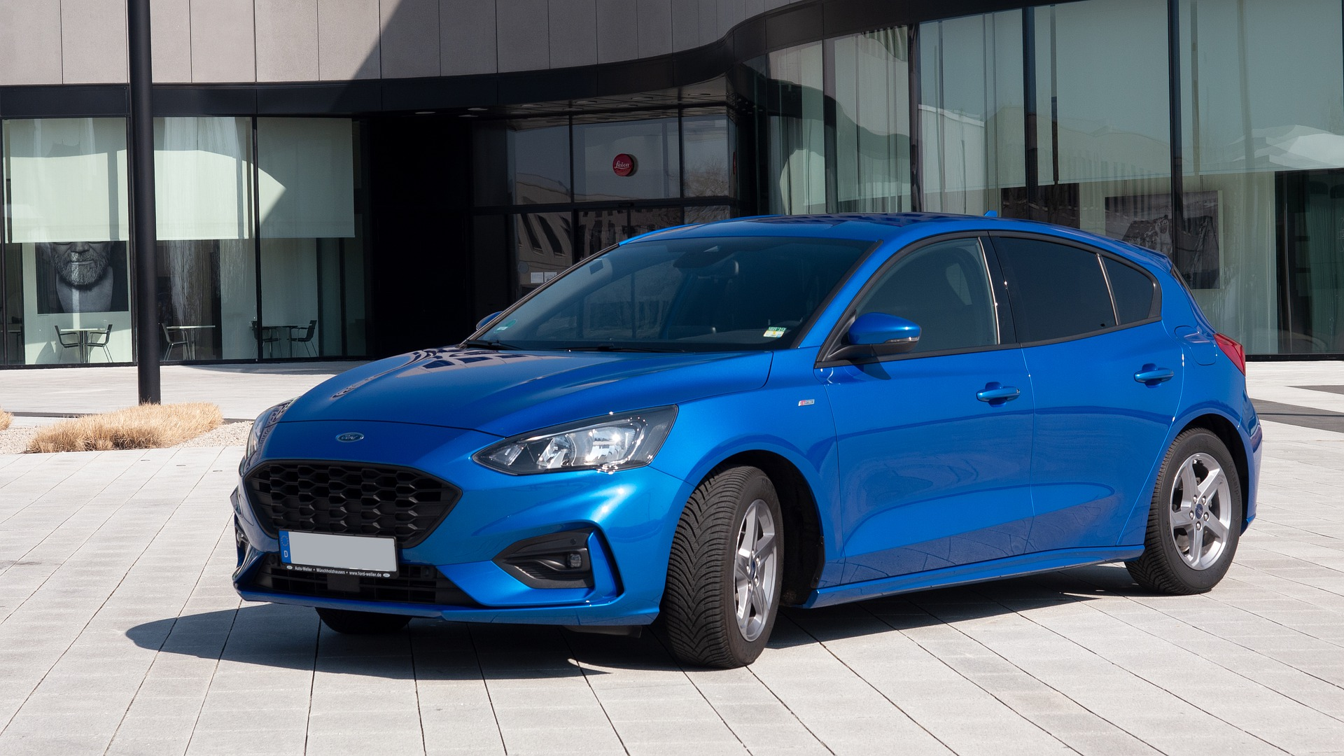 Blue Ford Focus parked outside building