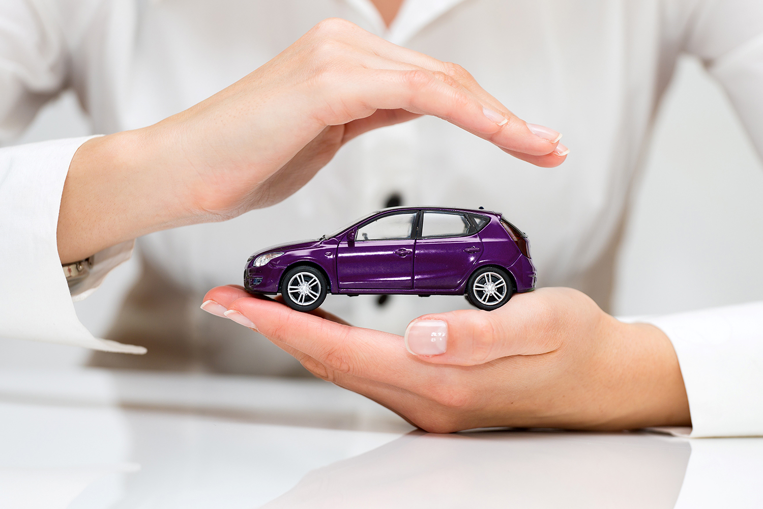 Hands holding purple toy car