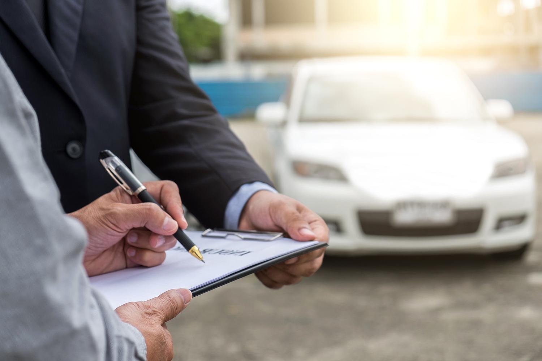 man signing a form at car dealership