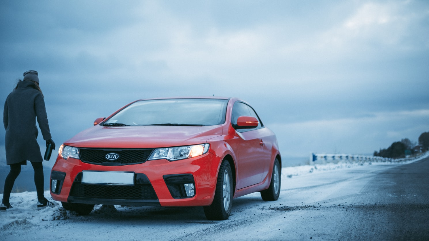 Red Kia parked on an icy road