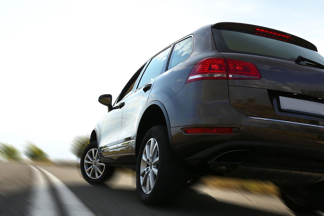 Black Kia Sportage driving uphill