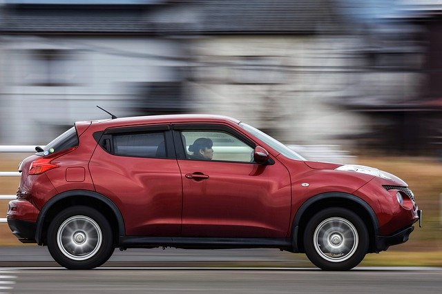 woman driving red nissan juke