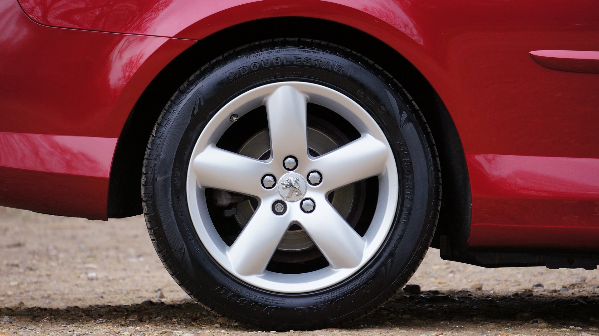 Red Peugeot car wheel with logo