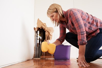 Woman cleaning after water damage. Protect your home during cold weather