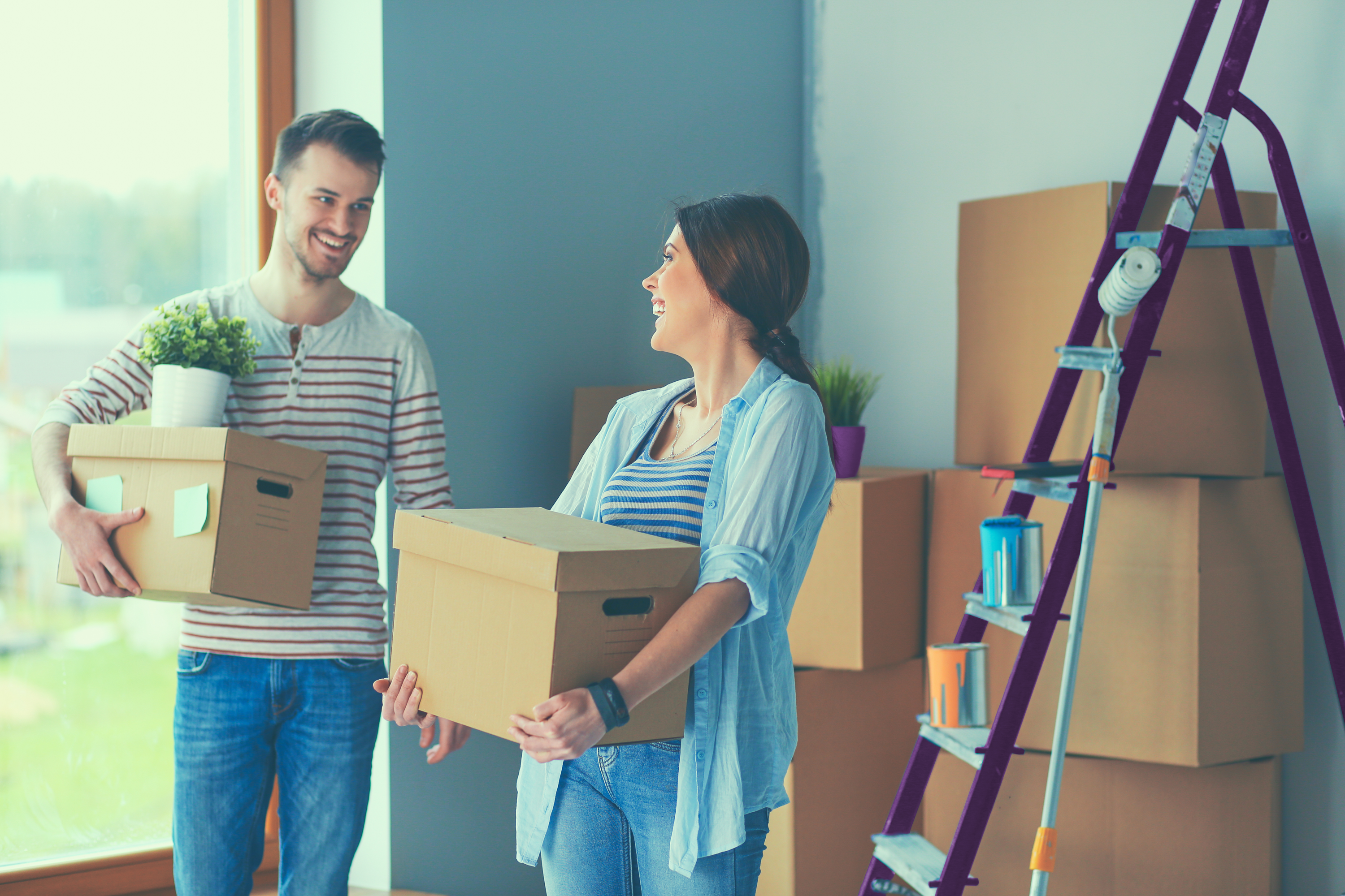 man and woman moving boxes into new home