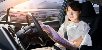 woman reading a book in an autonomous car