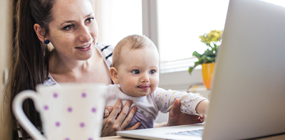 woman holding baby in front of laptop