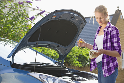 woman checking her car's oil level