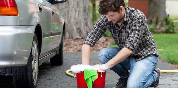 man washing his car preparing to sell it