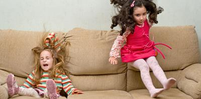 two young children jumping on sofa