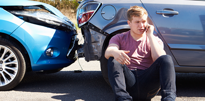 young man on phone to insurance company following car accident