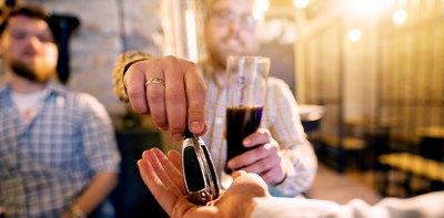 man drinking alcohol handing car keys to a friend