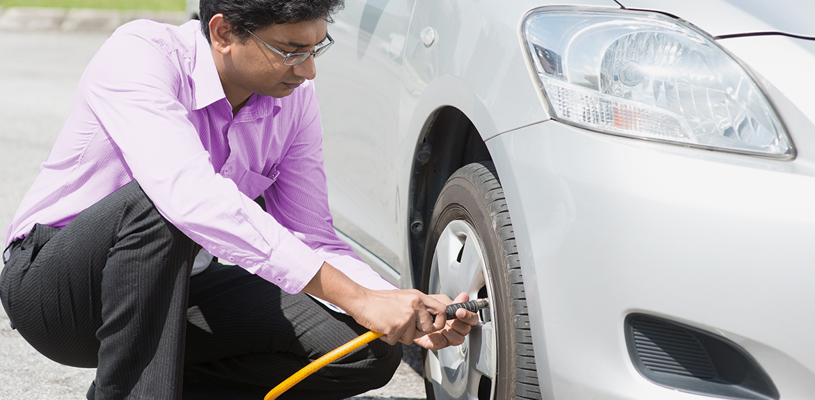 man checking the tyre pressure on his car