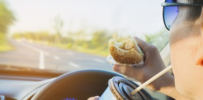 man eating and drinking while driving