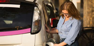 woman recharging electric car