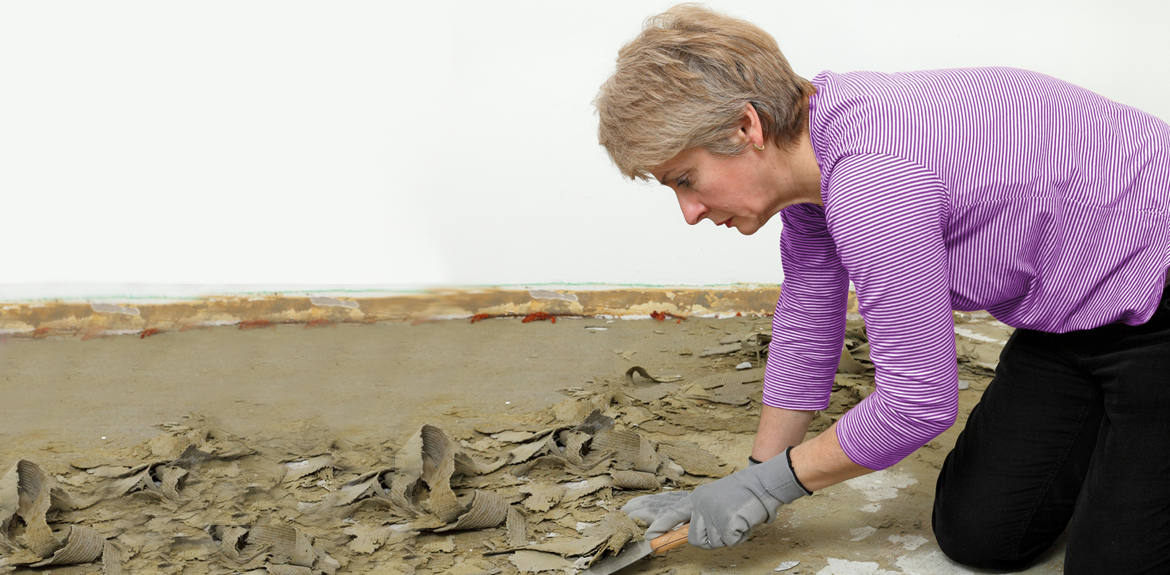 woman removing water damaged floor with scraper