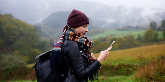 woman dressed for cold weather checking her phone