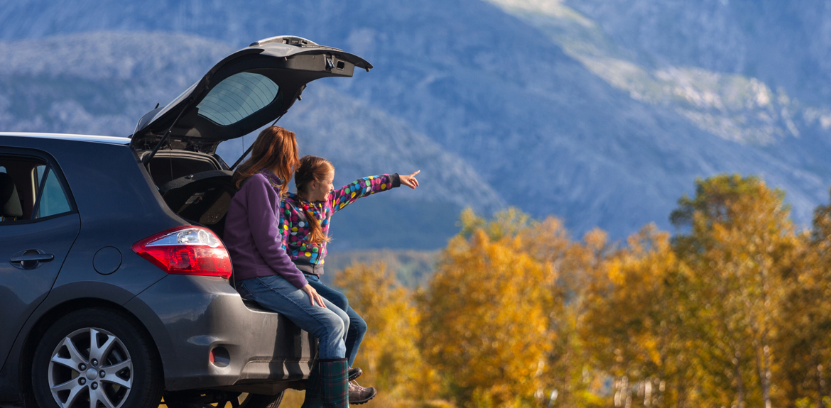 mother and daughter driving car abroad