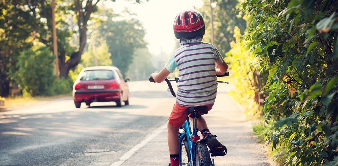 Child riding his bicycle along a main road