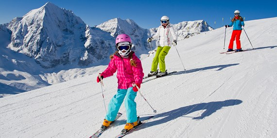 young girl and family skiing on slopes on holiday