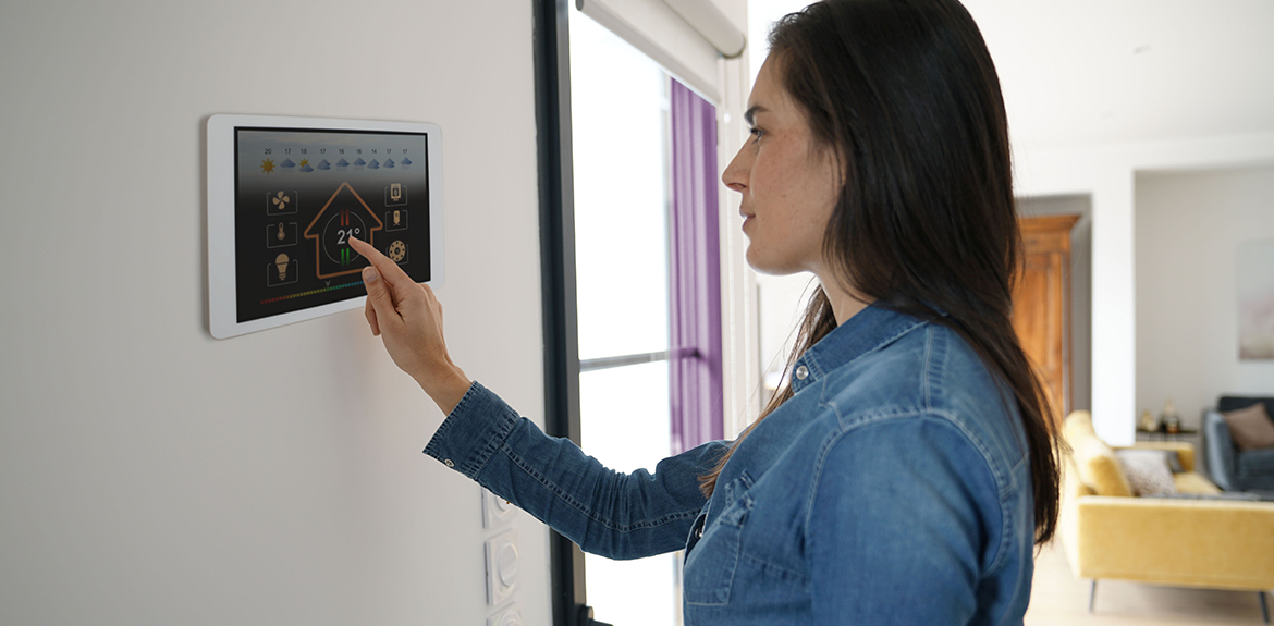 woman operating home security tablet device on the wall
