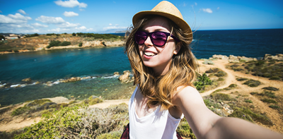 woman taking selfie for social media on sunny holiday