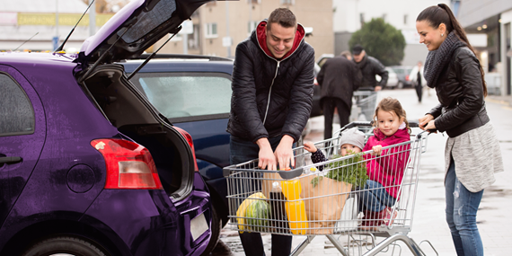 young family loading car with supermarket shopping