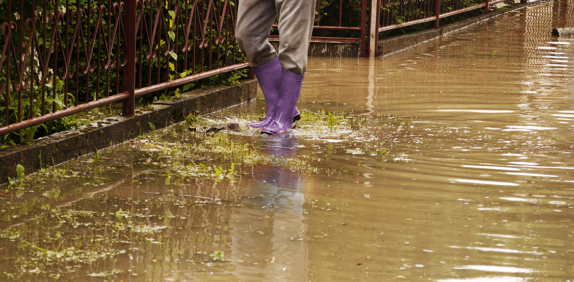 person wearing wellies wading through floodwater