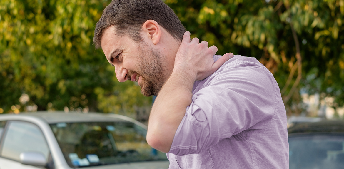 man holding neck in pain after car accident
