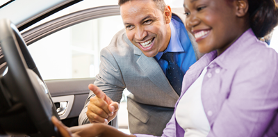 salesman showing off car features to a customer