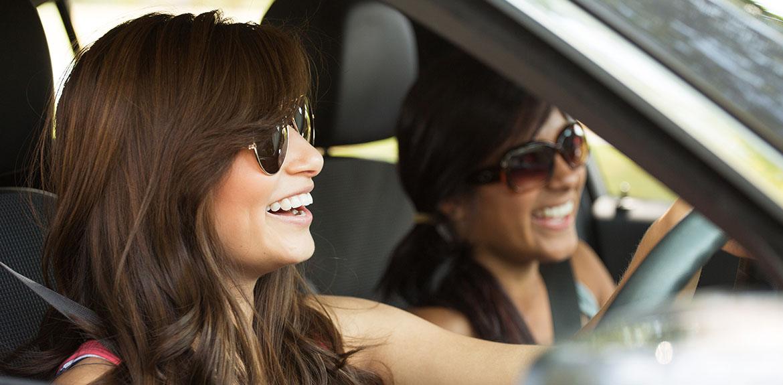 women laughing car