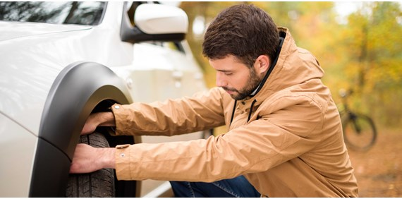 man checking tyre on car