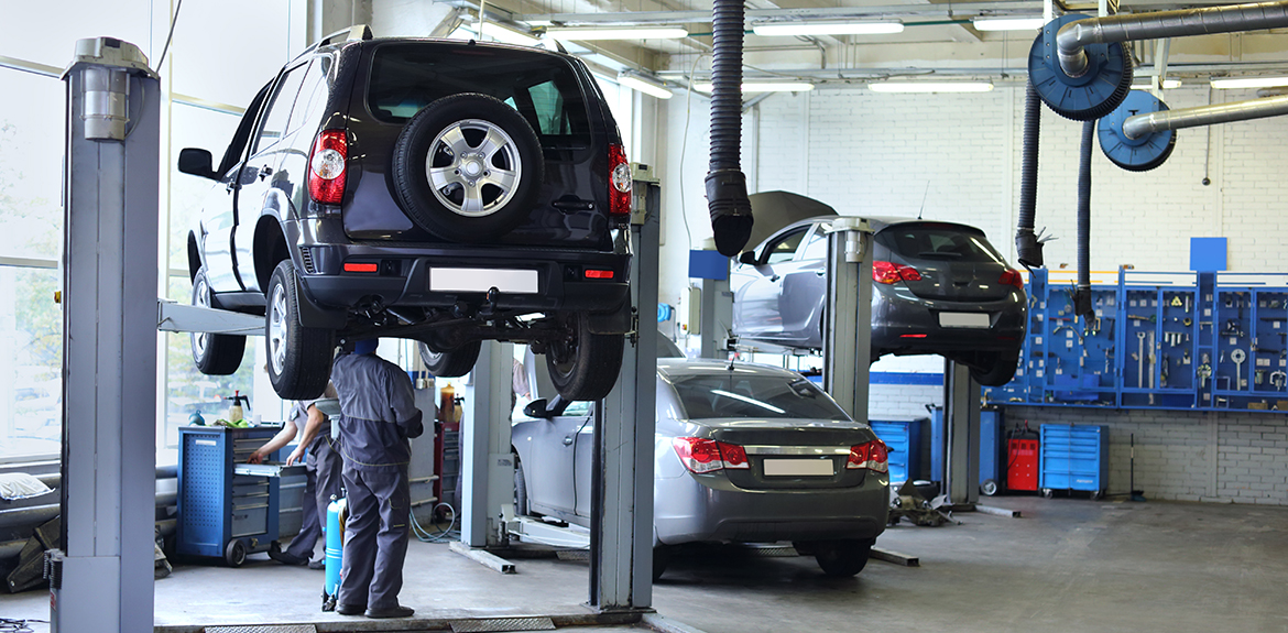 man inspecting cars in garage