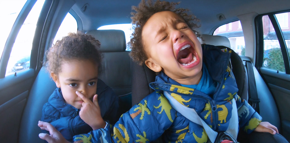 two children arguing and screaming in car seat