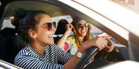 young women driving smiling sunglasses