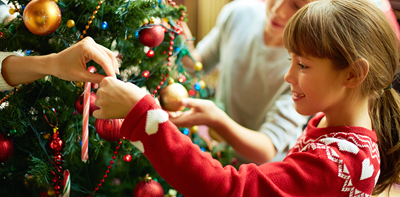 young girl hanging decorations on Christmas tree
