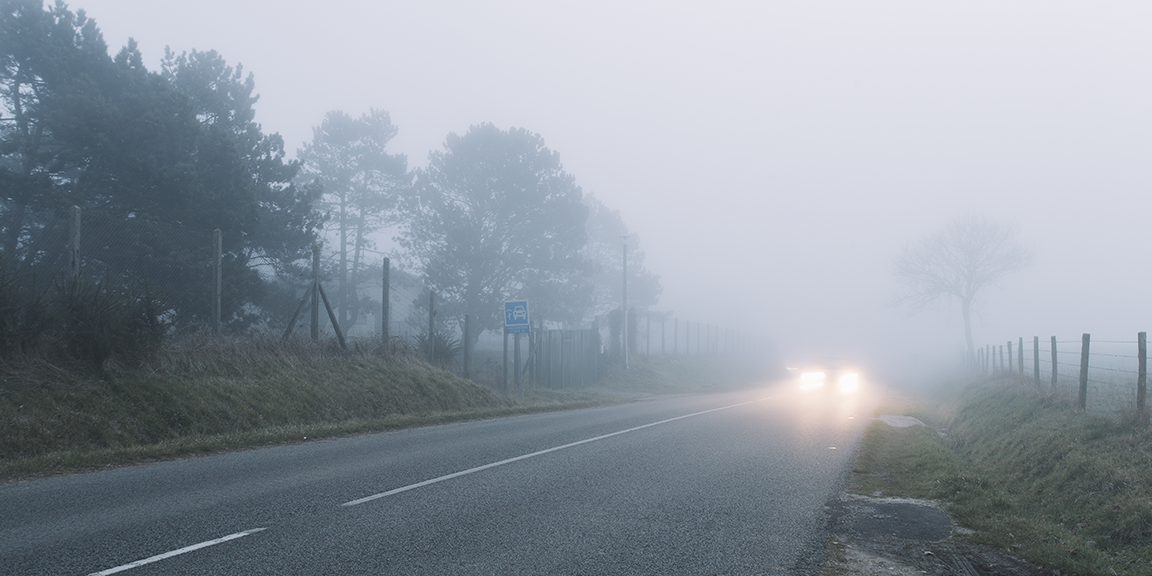 car with headlights on driving in fog