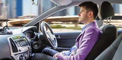 Man sat in the driver's seat of an autonomous car