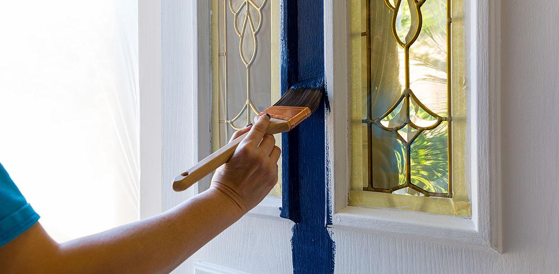 man painting front door blue